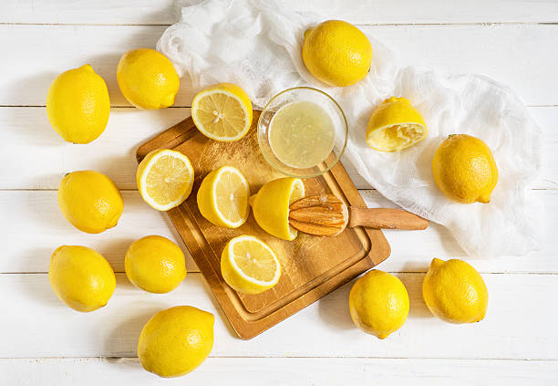 Lemons and citrus squeezer on a wooden background Lemons and citrus squeezer on a table lemon juice stock pictures, royalty-free photos & images