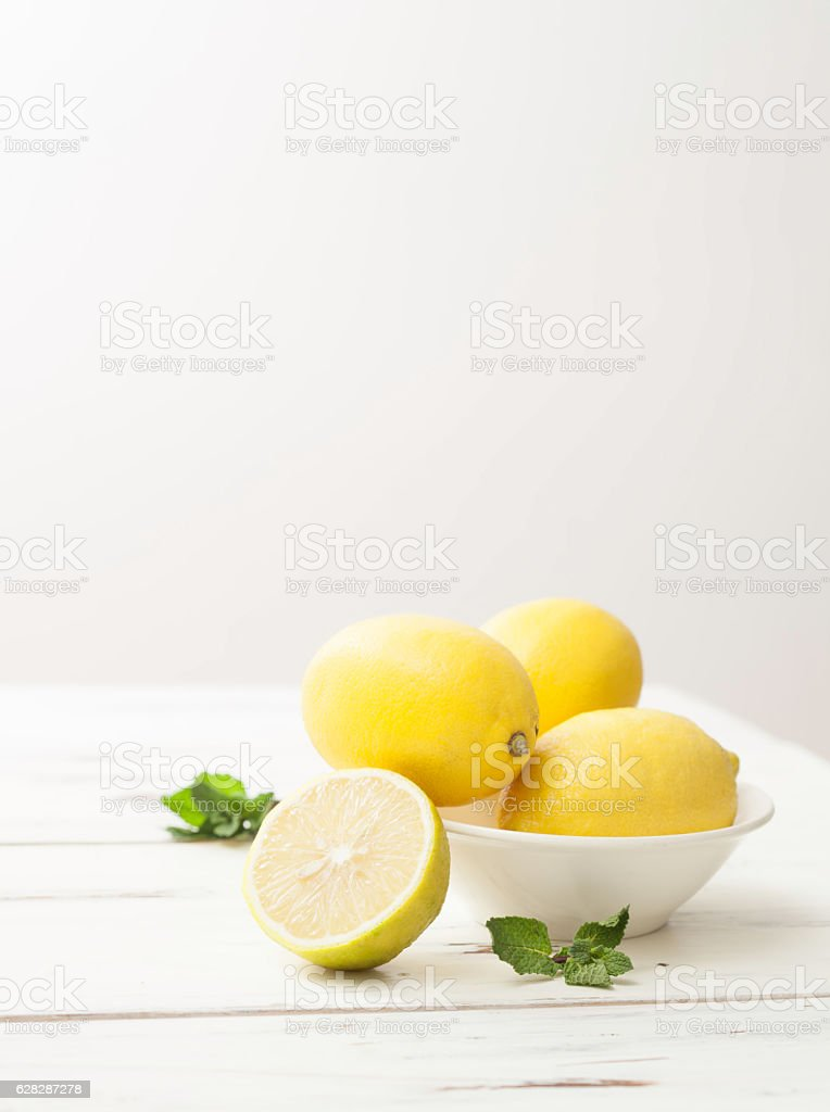lemons and mint on white wooden table stock photo