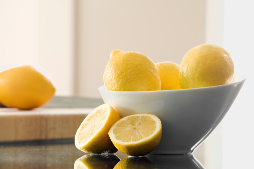 Lemons in a bowl and cut up on counter