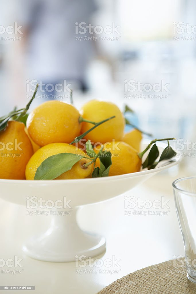 Lemons in bowl on table, person standing in backgroundclose-up foto royalty-free