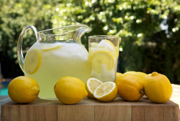 Lemons next to a pitcher and glass of fresh made lemonade  stock photo