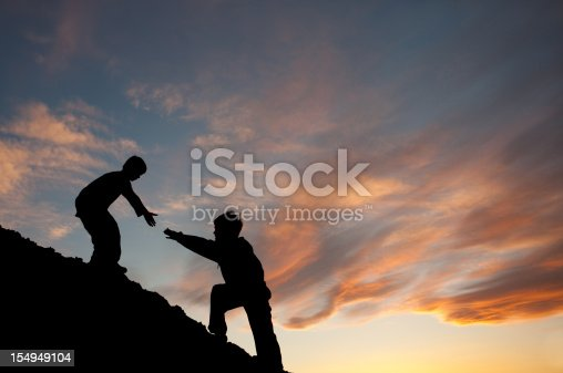 Concept image of two boys climbing a hill with one reaching out to help the other. Silhouette. Elementary age children. Side view. Teamwork concept. Additional themes in the image are: helping, friendship, siblings, brothers, lending a hand, assisting, caring, support, climbing, hiking, fitness, love, reaching out, neighborly, giving, stretching, gratitude, care, relationships, and family.