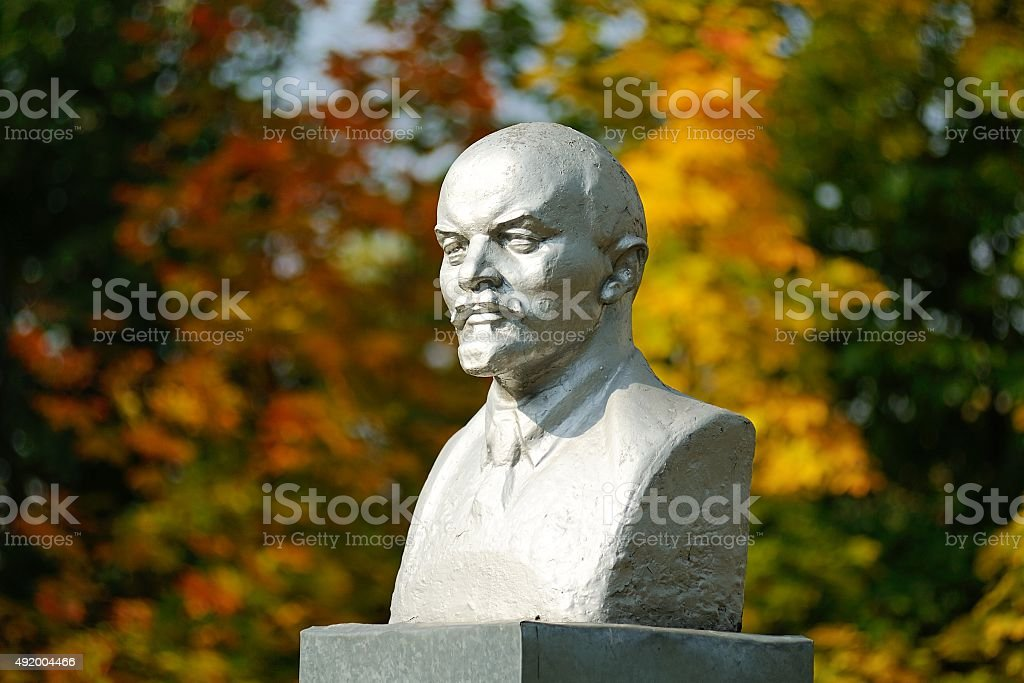Lenin bust monument with autunm leaves on the background stock photo