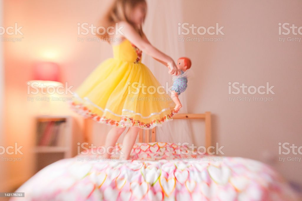 Lens baby image of little girl spinning with her doll royalty-free stock photo