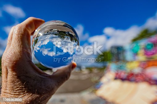 istock Lens ball held by male hand reflecting a blue sky with white clouds, green trees with a wall with an explosion of colors 1269363893