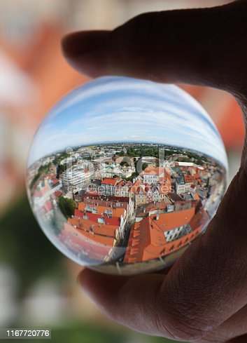 Lens ball with reflection of Hradec Kralove city at morning light from white tower. Sky with white clouds. Historical city in Czech republic.