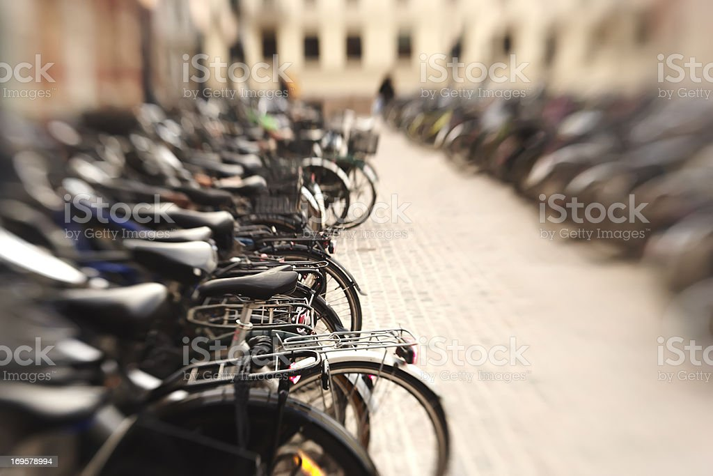 A lens blurred photo of lots of parked bikes. Symbolic content. royalty-free stock photo