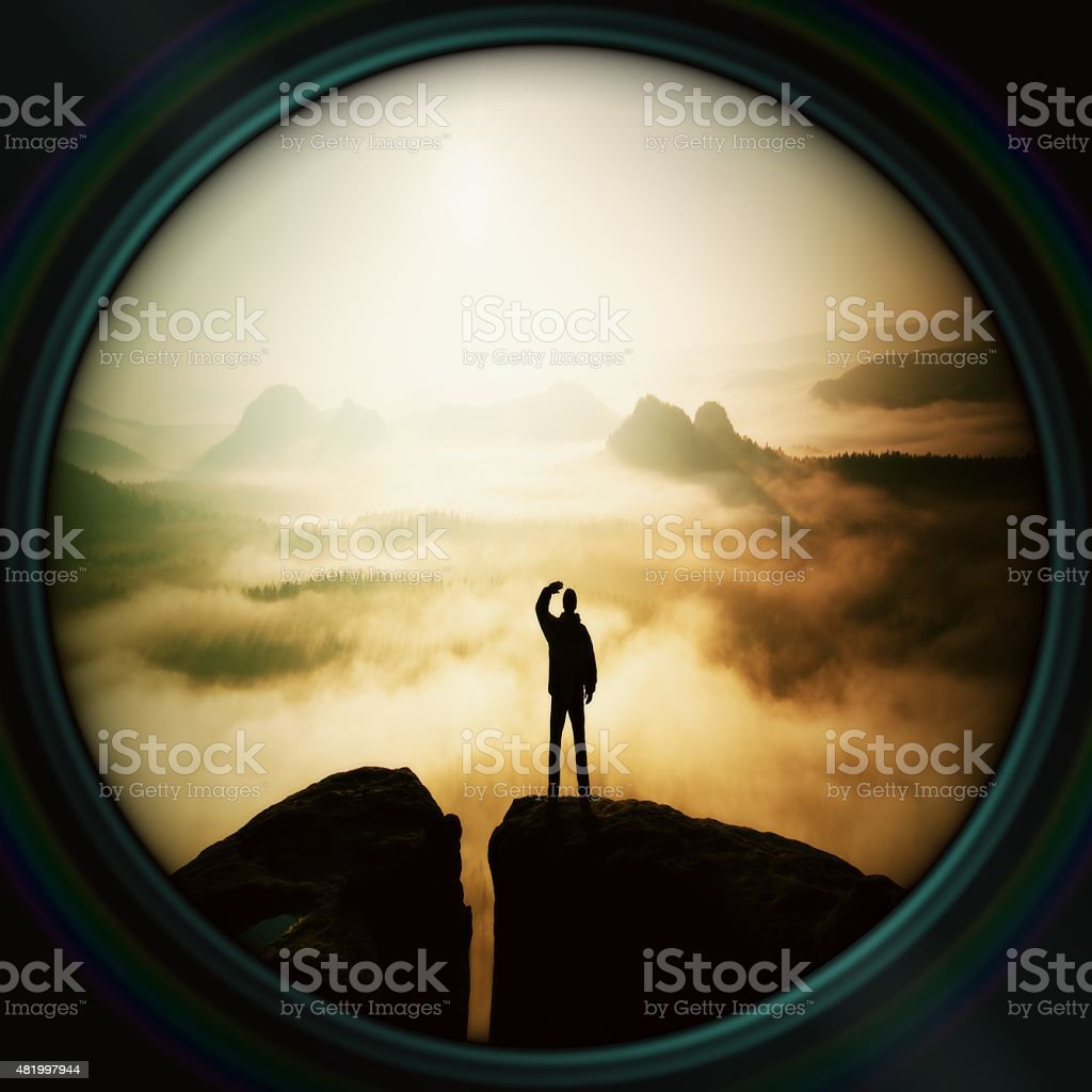 Lens effect. Alone hiker on rock empire, morning misty valley stock photo