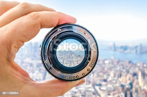 Hand holding camera lens in New York City. USA