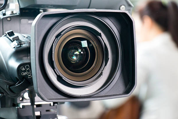 Lens of a Movie Camera wit an Actress in Background stock photo