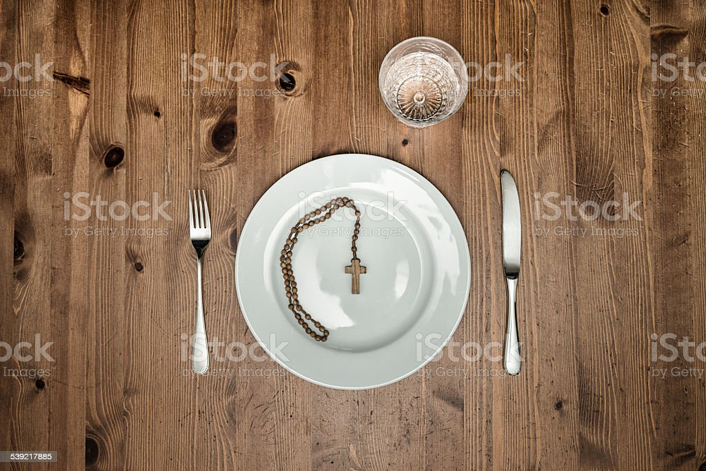 Lent - empty plate with a rosary stock photo