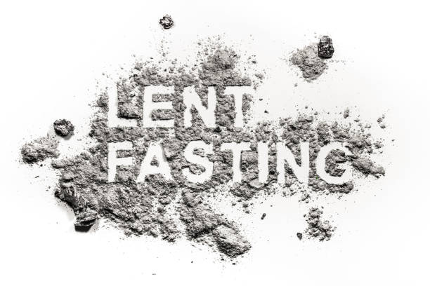 Lent fasting word written in ash, sand or dust stock photo