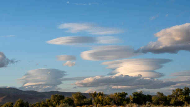 lenticular clouds over mountain range Lenticular clouds over mountain range from Lahontan State Recreation Area, Silver Springs, Nevada, USA on September 27, 2019. lenticular cloud stock pictures, royalty-free photos & images