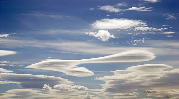 Lenticular Clouds Rare lenticular clouds, with their unique layered, round appearance. Such clouds are formed by winds flowing over mountain ranges. lenticular cloud stock pictures, royalty-free photos & images