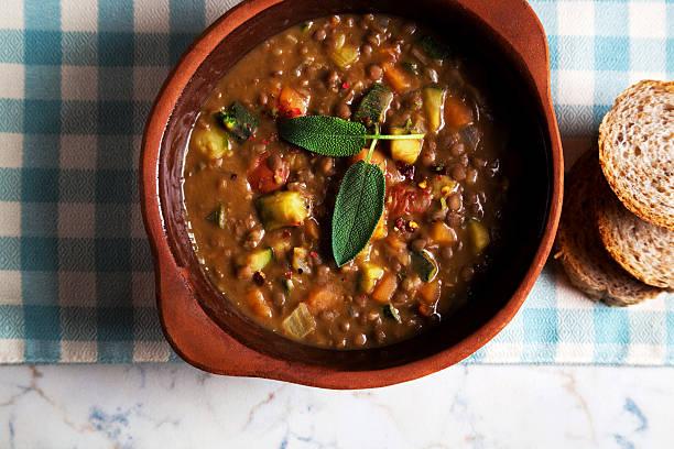 linsensuppe mit knusprigem brot auf dem tisch - hausgemachte tomatensuppen stock-fotos und bilder