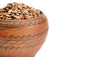 Lentils in a clay pot isolated on white background. Healthy food. Free space for text.