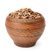 Lentils in a clay pot isolated on white background. Healthy food.