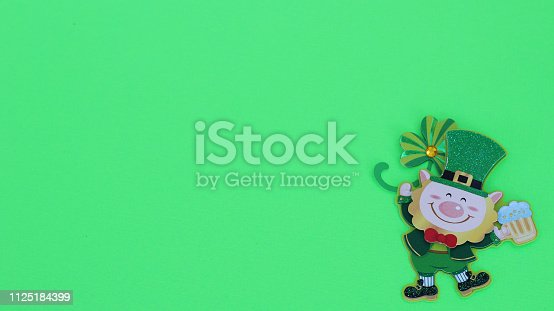 istock leprechaun holding a beer laying flat on a green background 1125184399