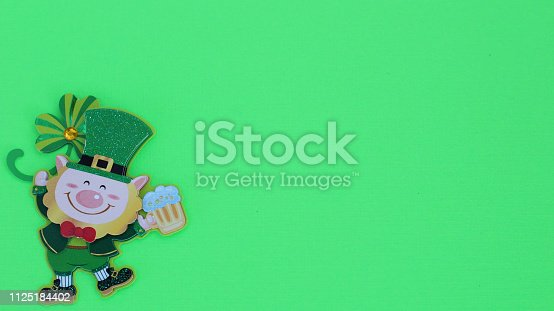 istock leprechaun holding a beer laying flat on a green background 1125184402