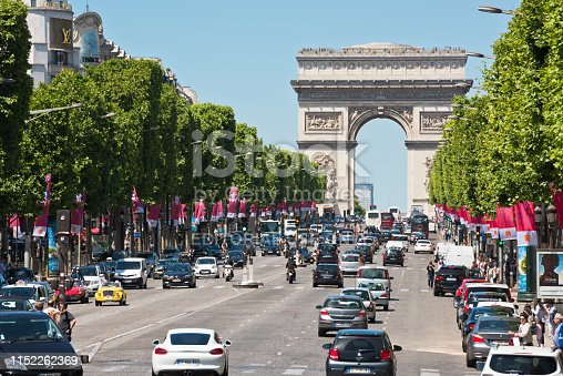France, Paris - June 06, 2015: Car road traffic on Les Champs-Elysees street in Paris with beautiful Arch of Triumph on background