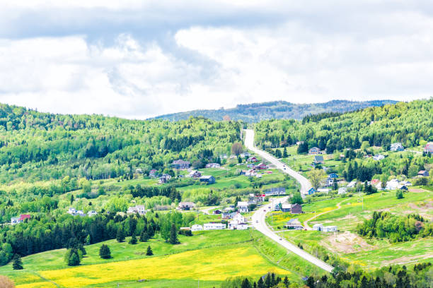 les eboulements, charlevoix, quebec, canada cityscape or skyline with main highway steep curvy road going vertically up, patch farm green dandelion field, scattered village houses - charming stock photos and pictures