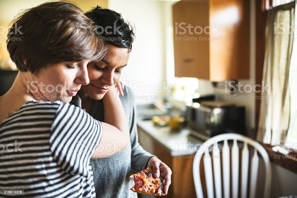 lesbian couple eating the pizza togetherness stock photo