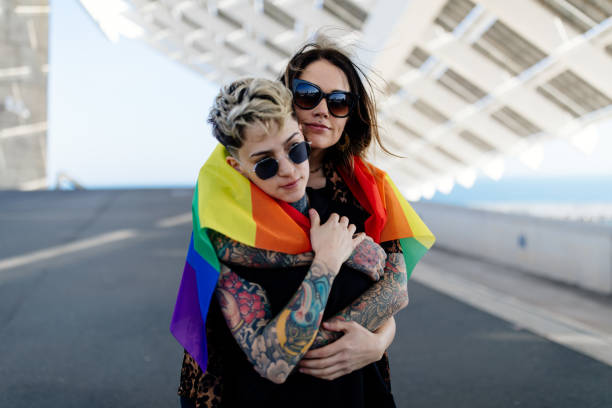 Lesbian couple embracing each other with LGBT pride rainbow flag stock photo