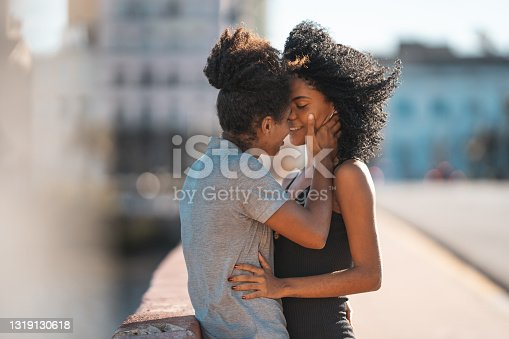 istock Lesbian couple kissing on the mouth outdoors 1319130618