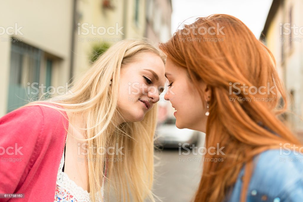 lesbian couple kissing outdoors stock photo