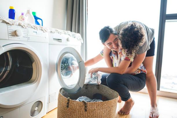 lesbisches paar lebensstil - waschmaschine fotos stock-fotos und bilder
