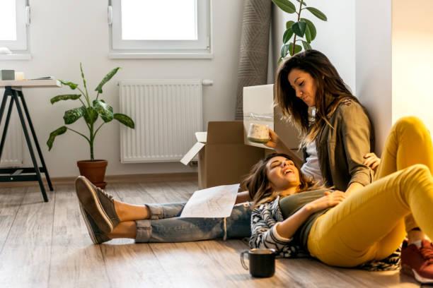lesbian couple making a new arrangement in apartment - coppia gay foto e immagini stock