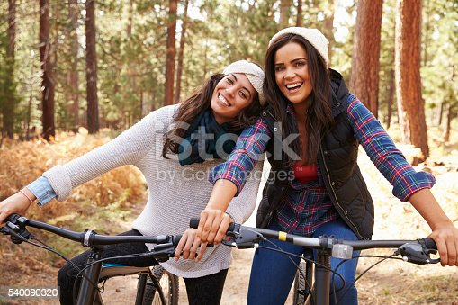 istock Lesbian couple on bikes in a forest look to camera 540090320