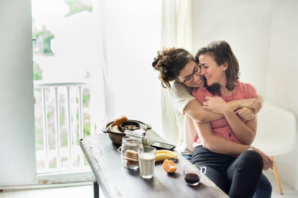lesbisch koppel samen binnenshuis concept - lesbische stockfoto's en -beelden