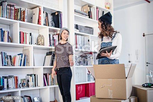 istock Lesbian couple unpacking cardboard box in living room 638367926