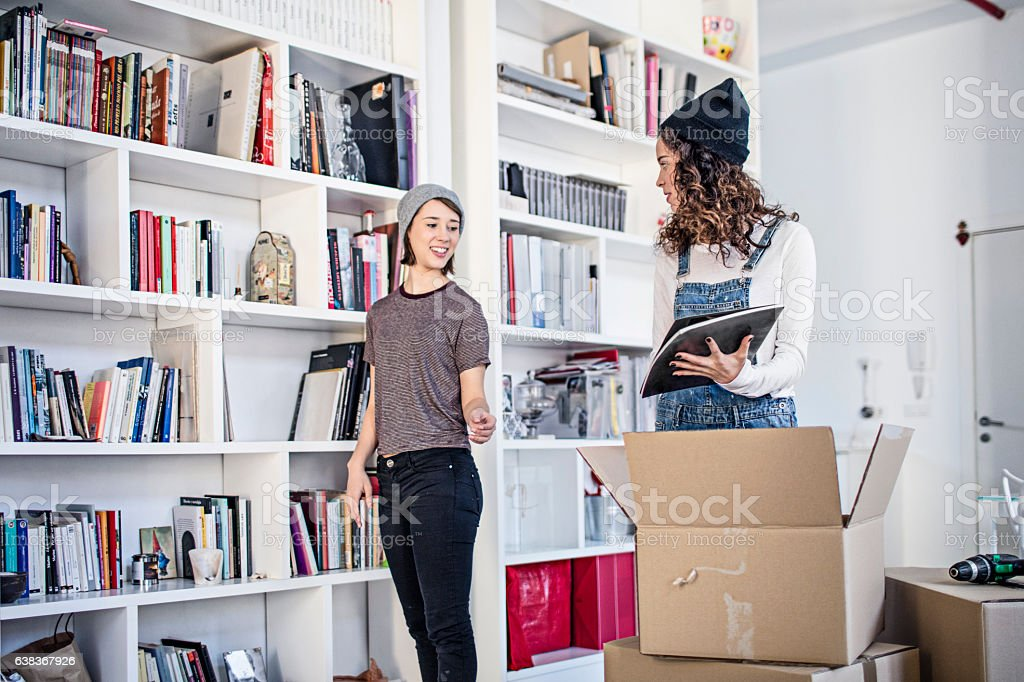 Lesbian couple unpacking cardboard box in living room stock photo