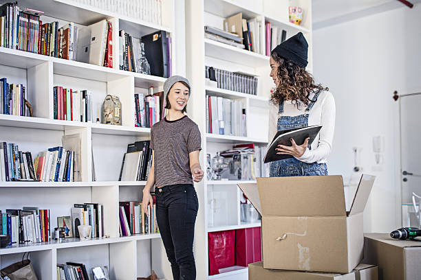 lesbian couple unpacking cardboard box in living room - disposition photos et images de collection