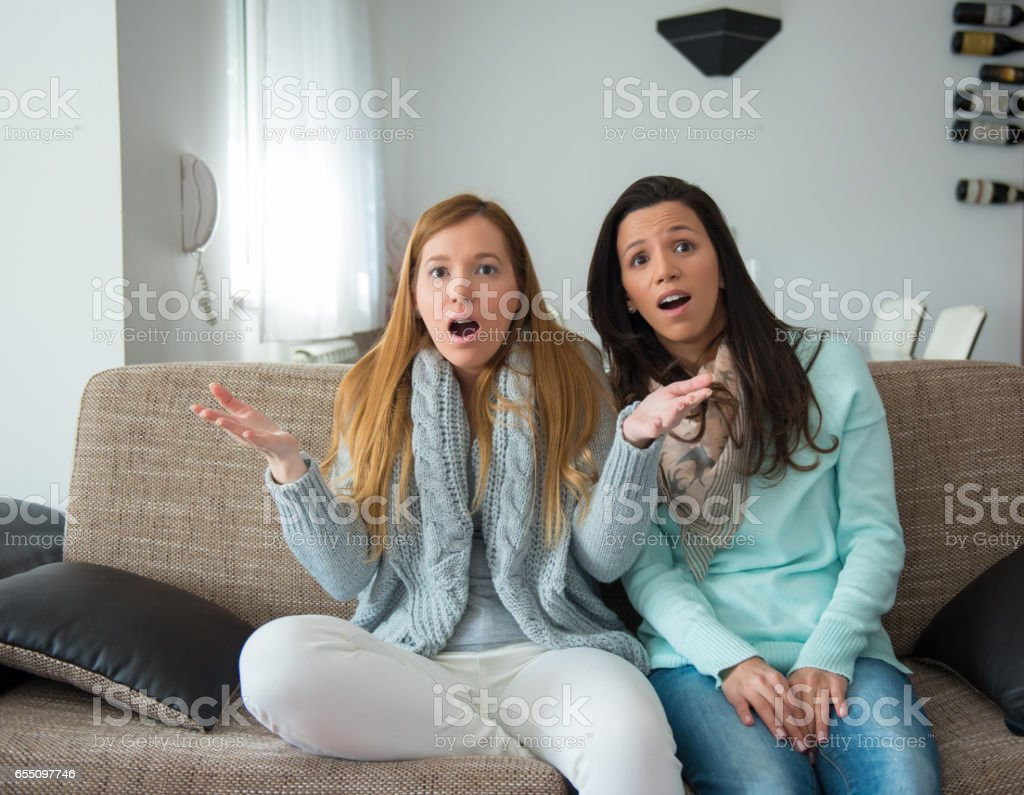 lesbian couple watching movie together, surpised stock photo