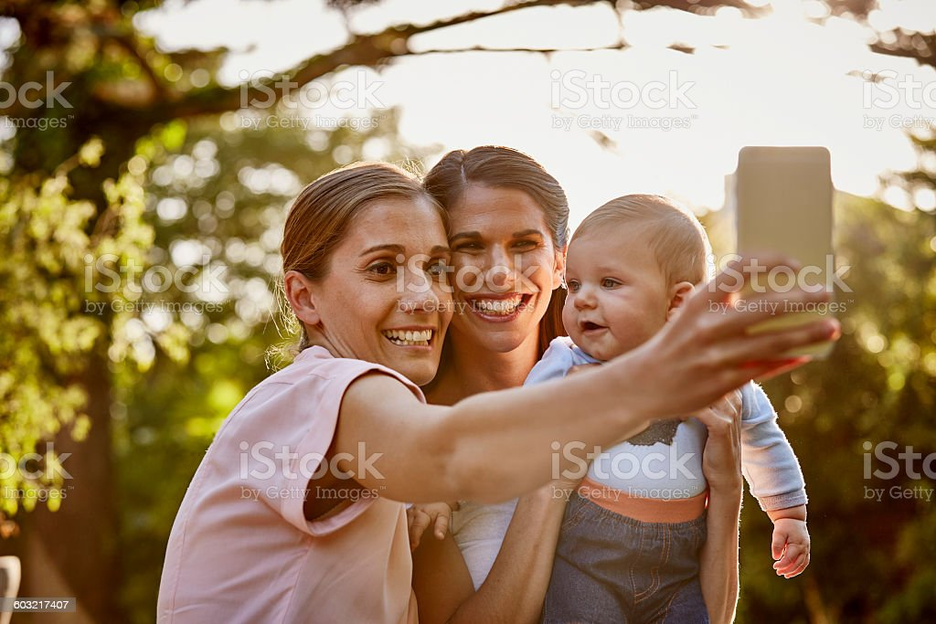 Lesbian couple with baby taking selfie in park stock photo