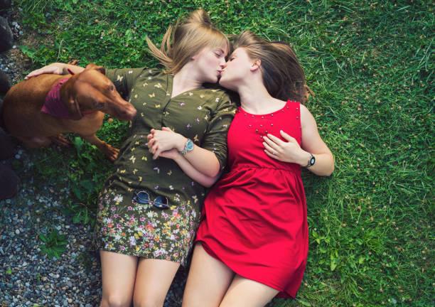 Pareja de lesbianas con perro tumbado en la hierba - foto de stock