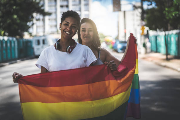 Lesbian Couple with Rainbow Flag Weekend Activities lgbtqi rights stock pictures, royalty-free photos & images