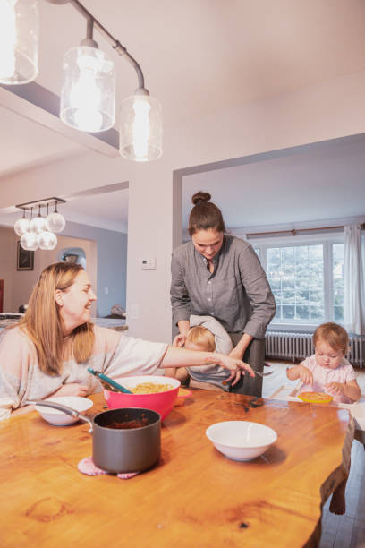 Lesbian couple with their children enjoying dinner at home LGBTQ, Family, Children, Togetherness - Young lesbian couple with their baby girl and boy enjoying the weekend dinner high seat stock pictures, royalty-free photos & images