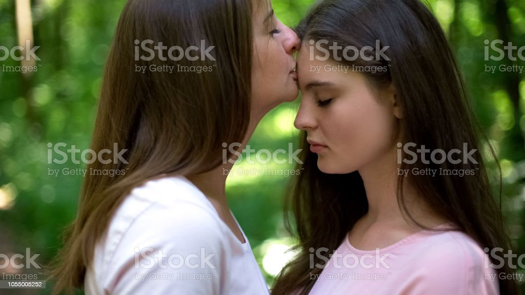 Lesbian kissing forehead of her loving girlfriend, gentle attitude, first  love - Stock image .