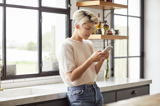 Smiling lesbian woman using smart phone. Female is text messaging while leaning on countertop. She is at home.
