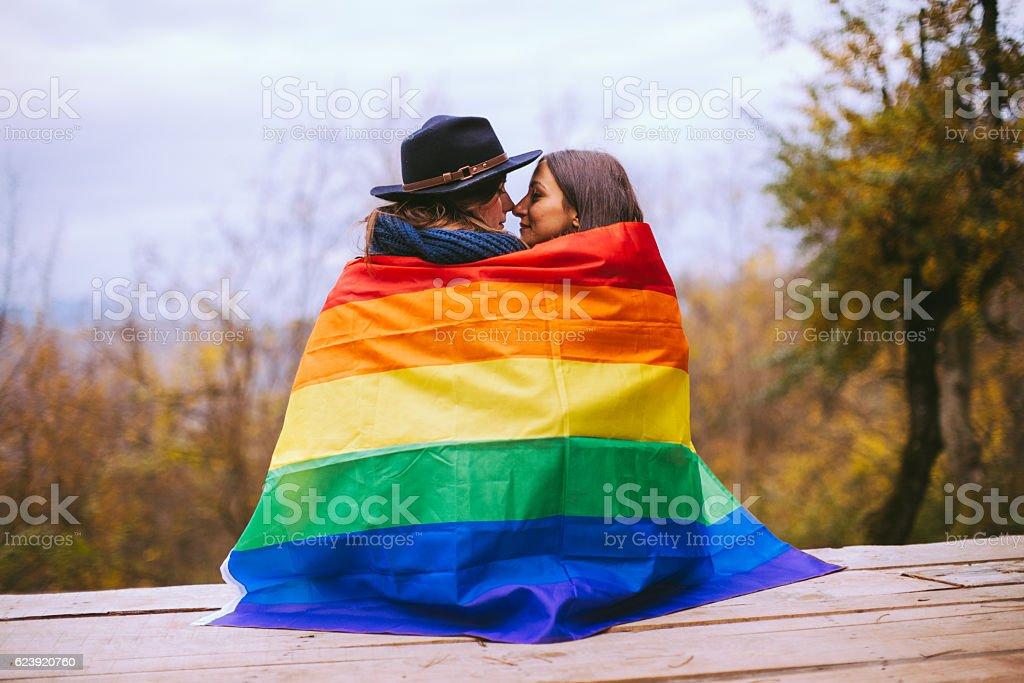 Lesbian Women Kissing Behind Rainbow Flag stock photo