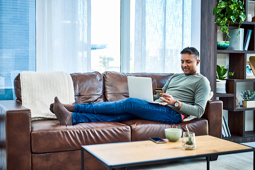 Shot of a man using a laptop and credit card on the sofa at home