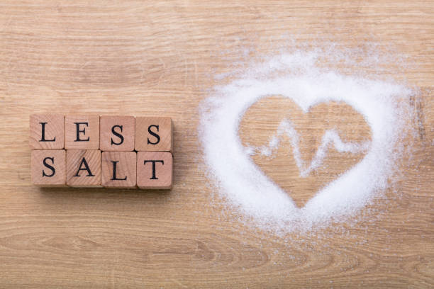 less salt near heart shape with heartbeat - sodium stock pictures, royalty-free photos & images