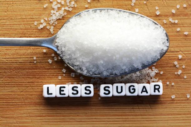 weniger zucker text von gefliesten buchstaben-blöcke und zucker haufen auf einem löffel, was darauf hindeutet, diät konzept - zuckerfreie lebensmittel stock-fotos und bilder