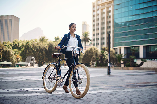 Shot of a young businesswoman traveling with a bicycle through the city