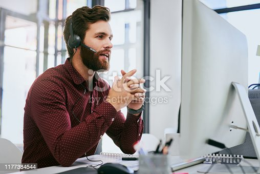 Cropped shot of a handsome young businessman sitting alone and wearing a headset while using a computer in the office