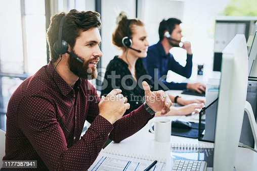 Cropped shot of a handsome young businessman wearing a headset and using a computer while sitting with his colleagues